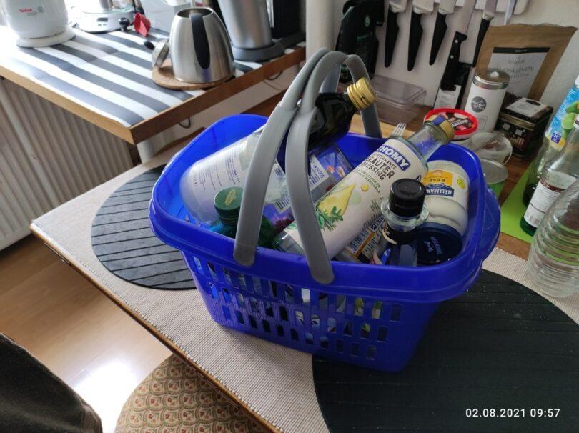Kleines Transportkörbchen, voll mit leeren Glasflaschen